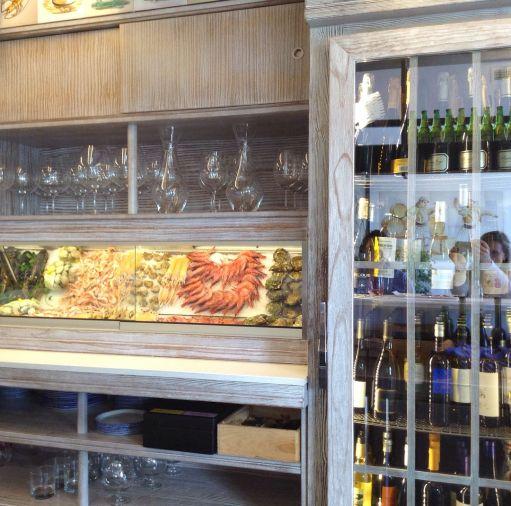 The fresh seafood cold case and wine fridge at Casa Carmela.