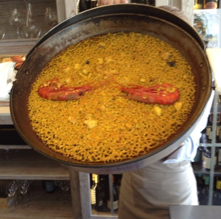 A pan full of fresh seafood paella displayed for photos.