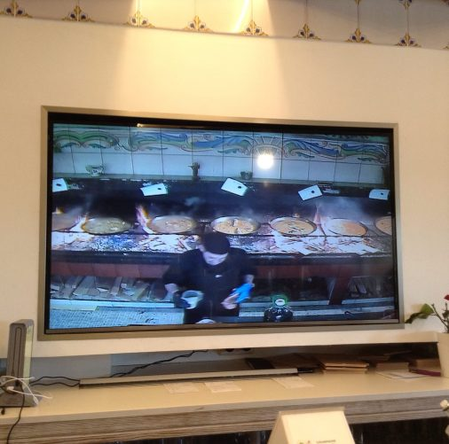 A TV showing 7 paella pans cooking atop wood burning stoves, and the cook in the process of making another.