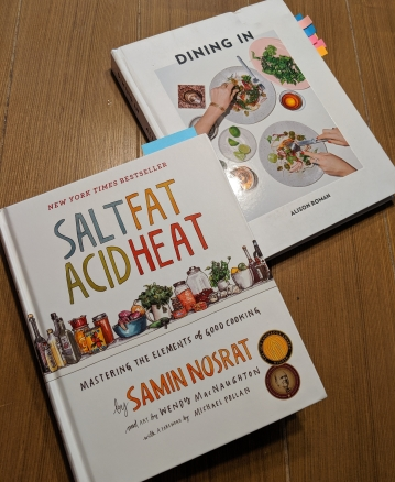 "Two cookbooks, ""Salt, Fat, Acid, Heat"" and ""Dining Out"" sit on the kitchen table."