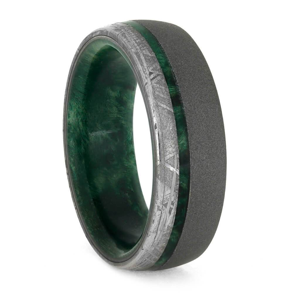 A picture of a men's wedding ring of green elder wood and meteorite.